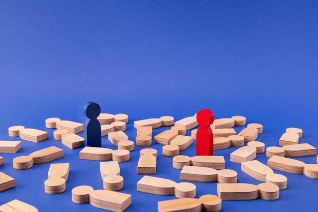 Dwie drewniane figurki liderów wygrywają biznesmenów stojących wśród anonimowych członków