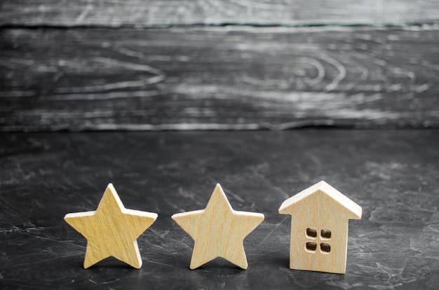 Dwie drewniane gwiazdy i dom. dwugwiazdkowy hotel lub restauracja. recenzja krytyka.