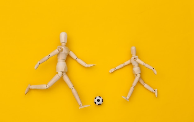 Dwie drewniane kukiełki grające w piłkę nożną z piłką na żółtym tle