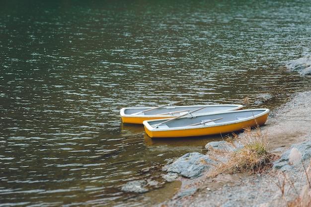 Dwie drewniane łodzie bez ludzi w cichym jeziorze, bez podróżnych i turystycznych skutków epidemii koronawirusa (covid-19)
