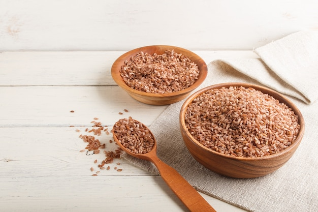 Dwie drewniane miski z niepolerowanym brązowym ryżem i drewnianą łyżką. widok z boku, lato.
