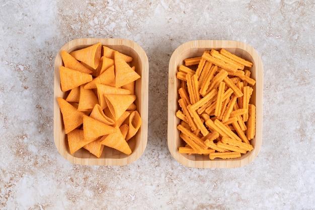 Dwie drewniane miski z trójkątnymi chipsami i paluszkami chlebowymi na kamiennej powierzchni.
