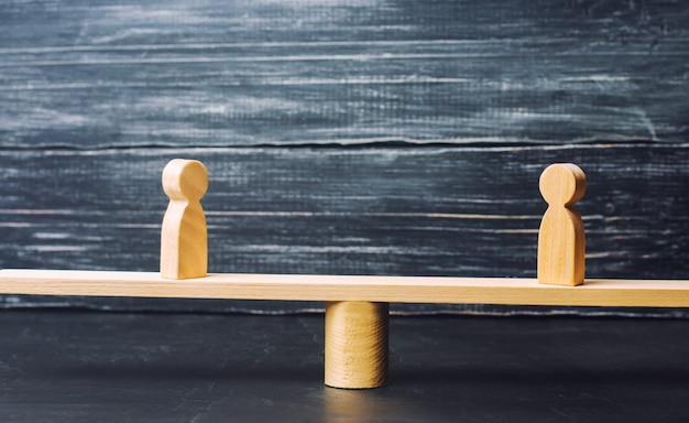 Dwie drewniane postacie stoją na szalach sprawiedliwości