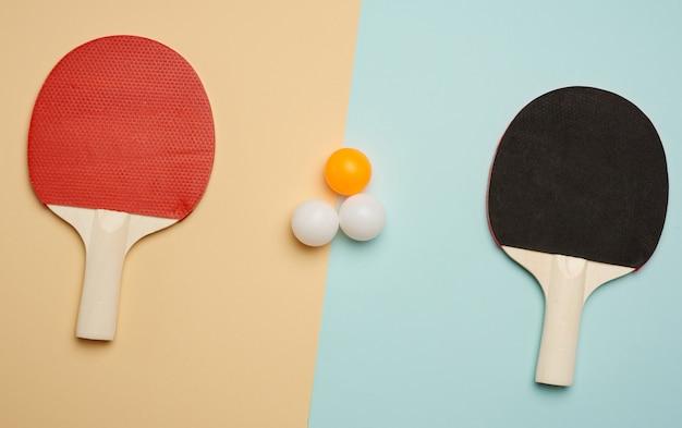 Dwie drewniane rakiety i plastikowe piłeczki do gry w tenisa stołowego