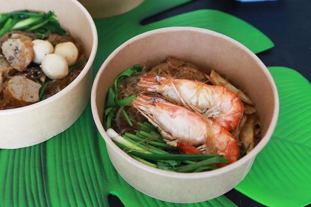 Dwie duże krewetki zapiekane z makaronem szklanym i warzywami, dobre menu w azjatyckiej restauracji, suchy makaron