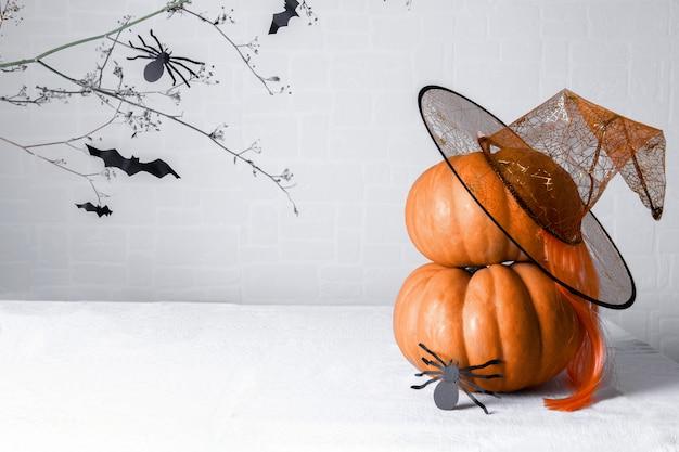 Dwie dynie z kapeluszem wiedźmy i pająkiem z czarnego papieru z przerażającym brunchem pełnym nietoperzy