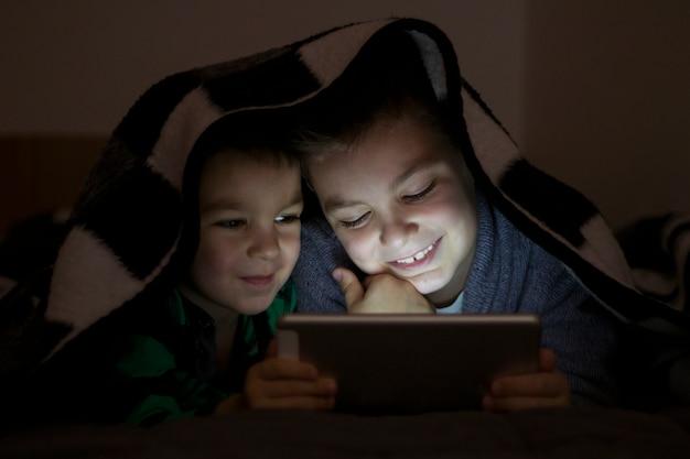 Dwie dzieci przy użyciu komputera typu tablet pod kołdrę w nocy. cute bracia z komputera typu tablet w ciemnym pokoju uśmiecha się.
