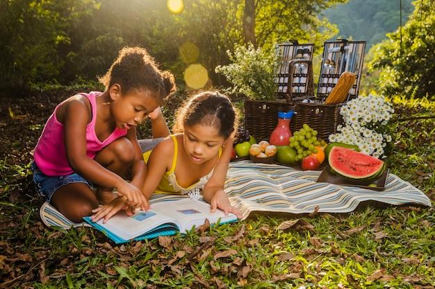 Dwie dziewczynki czyta na ściereczkach piknikowych