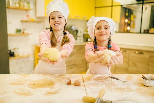 Dwie dziewczynki gotuje w czapkach pokazuje kulki ciasta