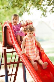Dwie dziewczynki w wieku przedszkolnym na zjeżdżalni na placu zabaw