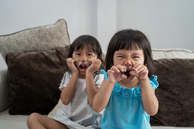 Dwie dziewczynki z malowanie twarzy na twarzy
