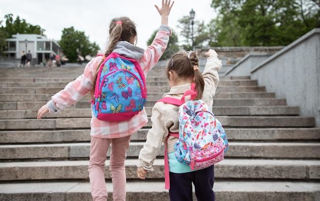 Dwie dziewczynki z pięknymi plecakami na plecach idą razem do szkoły. koncepcja przyjaźni z dzieciństwa.