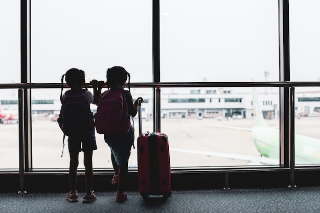 Dwie dziewczyny azjatyckie dziecko z plecakiem patrząc na samolot i czekając na wejście na pokład na lotnisku