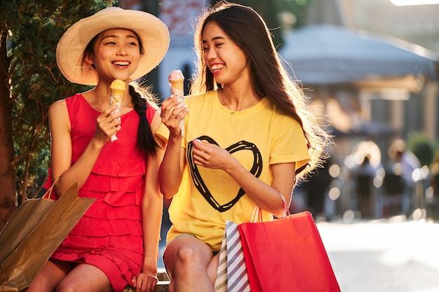 Dwie dziewczyny azjatyckie jedzenie lodów o zachodzie słońca w ławce miejskiej