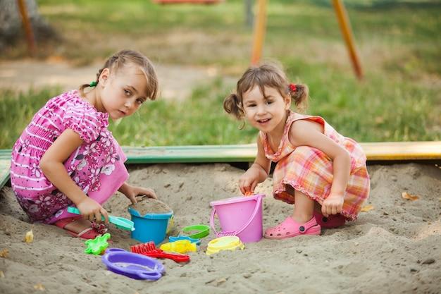 Dwie dziewczyny bawią się w piaskownicy na placu zabaw