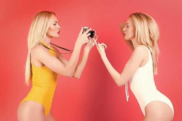 Dwie dziewczyny bliźniaczki fotografów z aparatem w stylu retro.