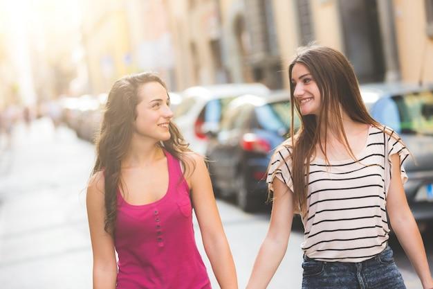 Dwie dziewczyny chodzą na ulicy trzymając się za ręce