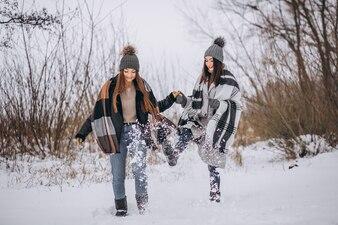 Dwie dziewczyny chodzić razem w winter park