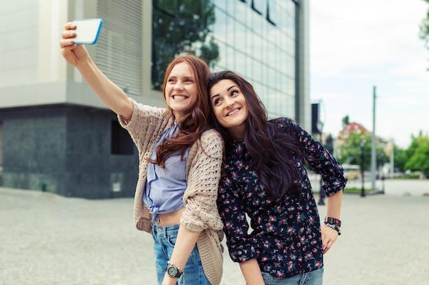 Dwie dziewczyny co śmieszne selfie na ulicy, wspólna zabawa