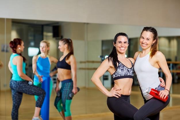 Dwie dziewczyny fitness na siłowni treningu grupowego