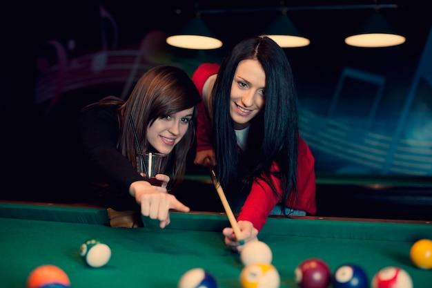Dwie dziewczyny grają w bilard