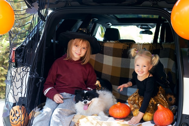 Dwie dziewczyny i pies z okazji halloween. bezpieczne halloween w kwarantannie. dwie siostry rodzeństwo siedzi w bagażniku samochodu ze zwierzakiem i bawi się z okazji halloween. cukierek albo psikus. zostań w domu