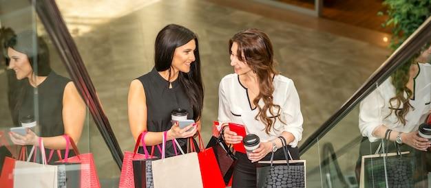 Dwie dziewczyny idą schodami ruchomymi z torbami na zakupy i rozmawiają w centrum handlowym