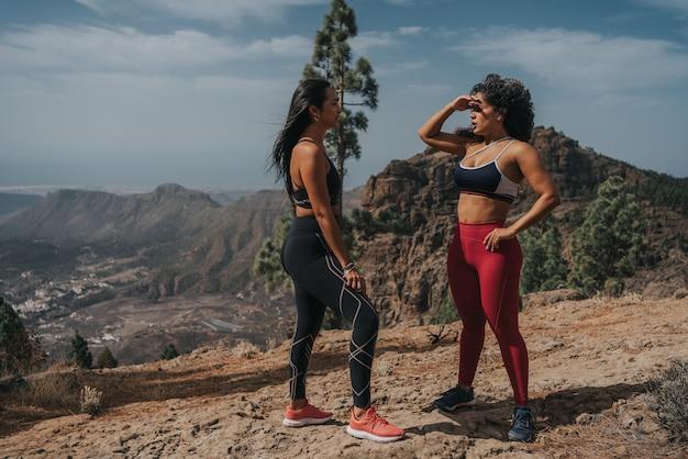 Dwie dziewczyny, jedna rasy białej, a druga czarna, uprawiają sport na wycieczce