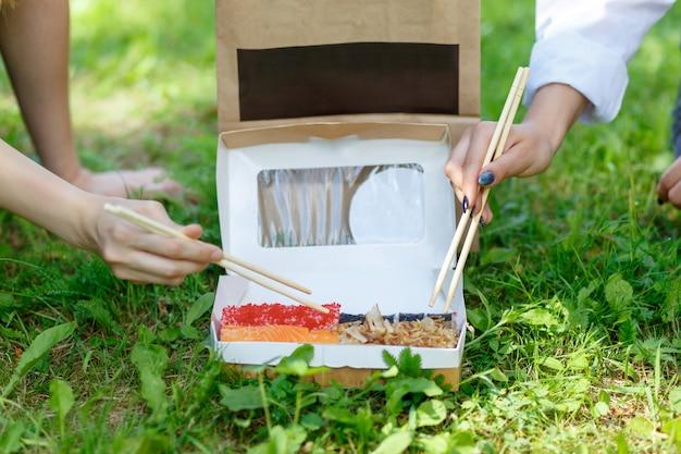 Dwie dziewczyny jedzą kolację z japońskim sushi na letnim pikniku