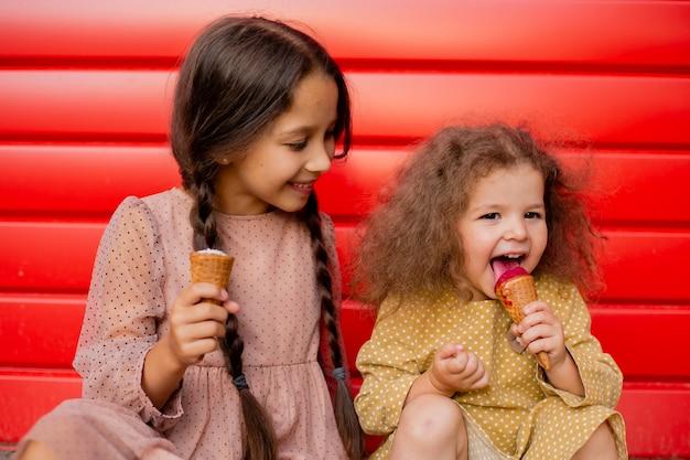 Dwie dziewczyny jedzą lody i wygłupiają się. nastolatek i mała dziewczynka na tle czerwonej ściany.