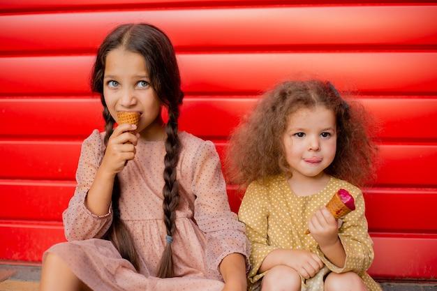 Dwie dziewczyny jedzą lody w pobliżu czerwonego płotu. jedna brunetka z dwoma warkoczykami, druga lekko kręcona
