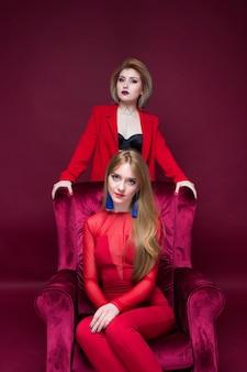 Dwie dziewczyny kobieta w czerwone ubrania lokalizacji czerwone krzesło i czerwonym tle
