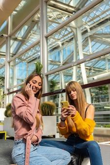 Dwie dziewczyny korzystają z telefonu siedzącego na schodach w szklarni miejskiej otoczonej roślinami