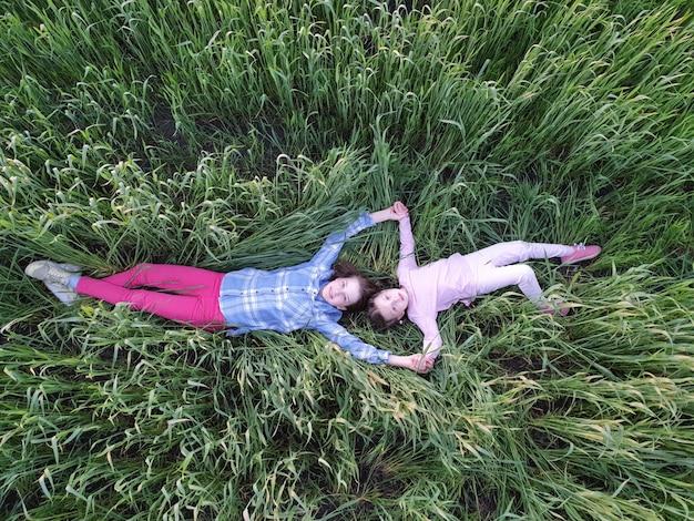 Dwie dziewczyny leżą w zielonej trawie, widok z góry, wolność w naturze