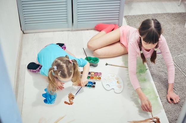 Dwie dziewczyny malują akwarelami i pędzlami na dużym papierze do rysowania na podłodze