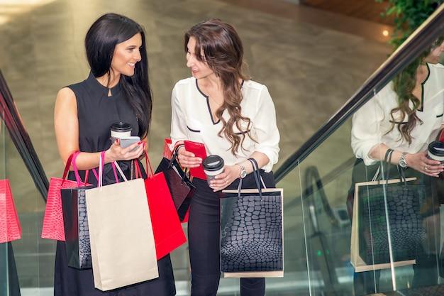 Dwie Dziewczyny Mówią O Zakupach Za Pomocą Smartfona Na Schodach W Centrum Handlowym I Trzymają Torby W Rękach. Premium Zdjęcia