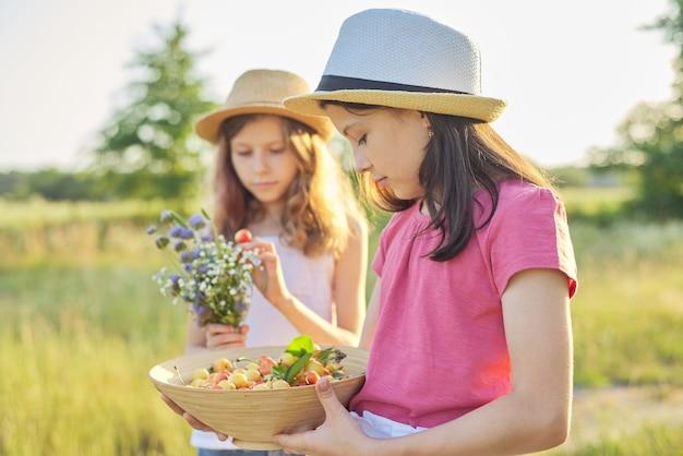 Dwie dziewczyny na łące w słoneczny letni dzień, spacerujące dzieci, z bukietem polnych kwiatów kosz żółtych wiśni. zdrowy styl życia i jedzenie, tło krajobraz zachód słońca