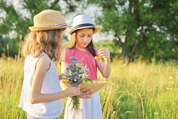 Dwie dziewczyny na łące w słoneczny letni dzień, spacerujące dzieci, z bukietem polnych kwiatów kosz żółtych wiśni