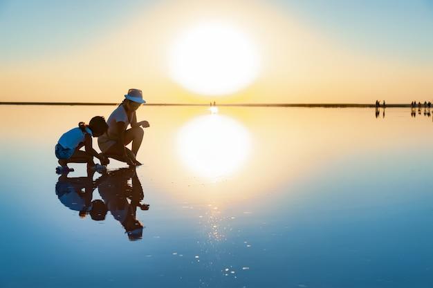 Dwie dziewczyny na pięknym przezroczystym jeziorze szukają czegoś na błyszczącej powierzchni