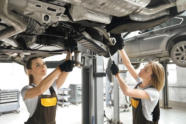 Dwie dziewczyny naprawiają podnoszone podwozie samochodowe za pomocą kluczy.