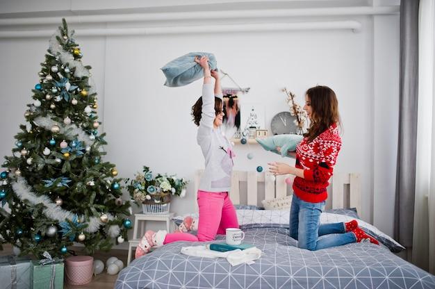 Dwie dziewczyny noszą zimowe swetry bawiące się na łóżku w pokoju z dekoracjami chrismas.