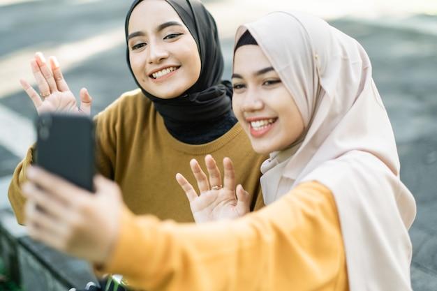 Dwie dziewczyny noszące hidżab z gestem dłoni podczas wykonywania wideorozmowy ze smartfonem po południu w parku