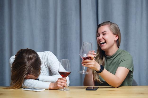 Dwie dziewczyny o europejskim wyglądzie o blond włosach siedzą przy stole, piją wino i śmieją się, odpoczywają w domu, piją alkohol