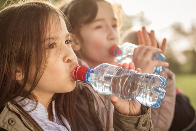 Dwie dziewczyny piją wodę z butelki