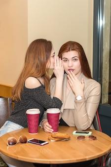 Dwie dziewczyny plotkują w barze-kawiarni