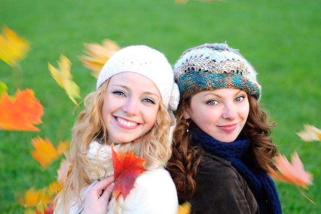 Dwie dziewczyny pod drzewem klonowym wyglądają na spadające liście. zamknij twarze