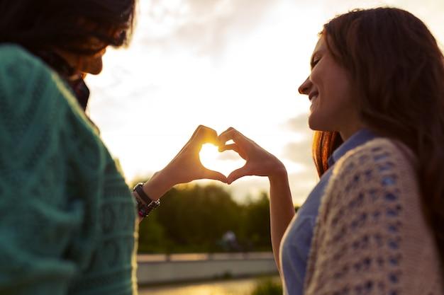 Dwie dziewczyny pokazują serce z rąk o zachodzie słońca
