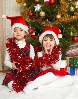 Dwie dziewczyny portret w dekoracji świątecznej zdobione jodły i prezenty