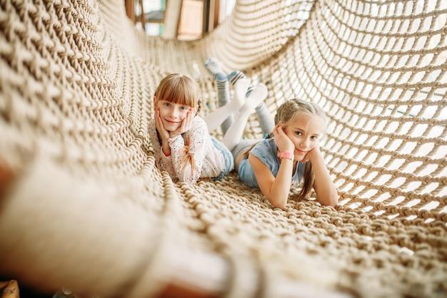 Dwie dziewczyny pozuje w siatce linowej, centrum zabaw dla dzieci