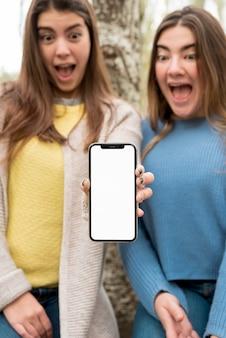 Dwie dziewczyny przedstawiające smartphone makieta